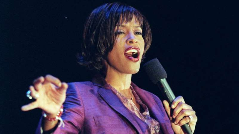 Whitney Houston holding a microphone: Whitney Houston, who drowned in 2012, is 12th on the list