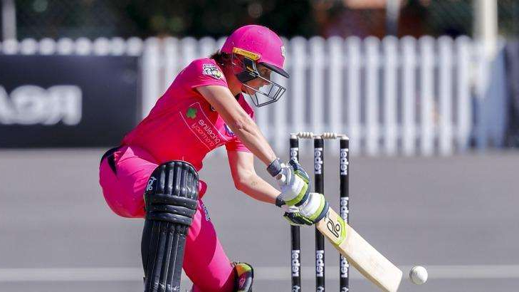 a person wearing a helmet: Alyssa Healy cracks a full delivery through the offside for the Sydney Sixers.