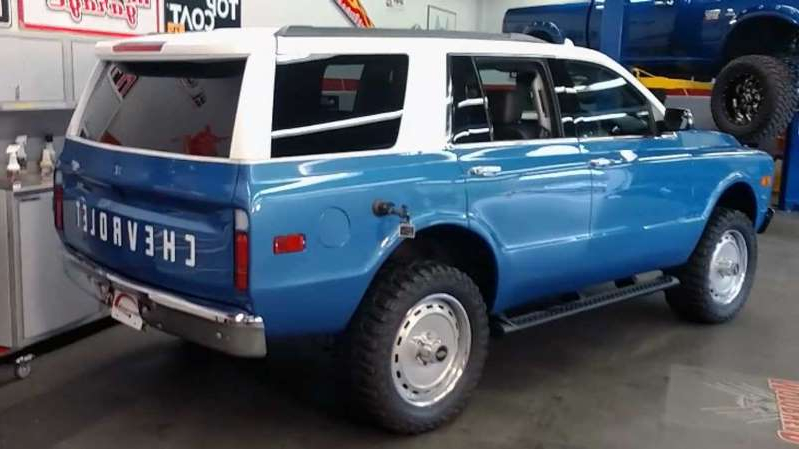 a truck is parked in front of a blue car: New Chevy Tahoe Transformed Into Classic Blazer For SEMA