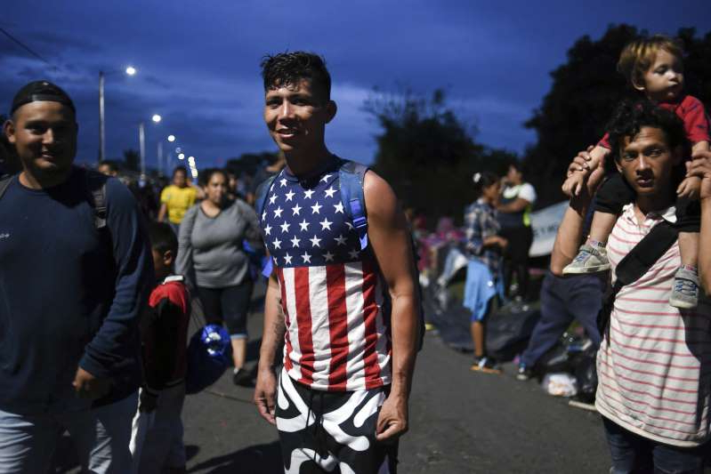 A young Honduran migrant wearing an american flag t-shirt, taking part in a caravan heading to the US, takes a rest as they arrive at the border crossing point with Mexico, in Ciudad Tecun Uman, Guatemala, on October 19, 2018. - Honduran migrants who have made their way through Central America were gathering at Guatemala's northern border with Mexico on Friday October 19, 2018 despite President Donald Trump's threat to deploy the military to stop them entering the United States.