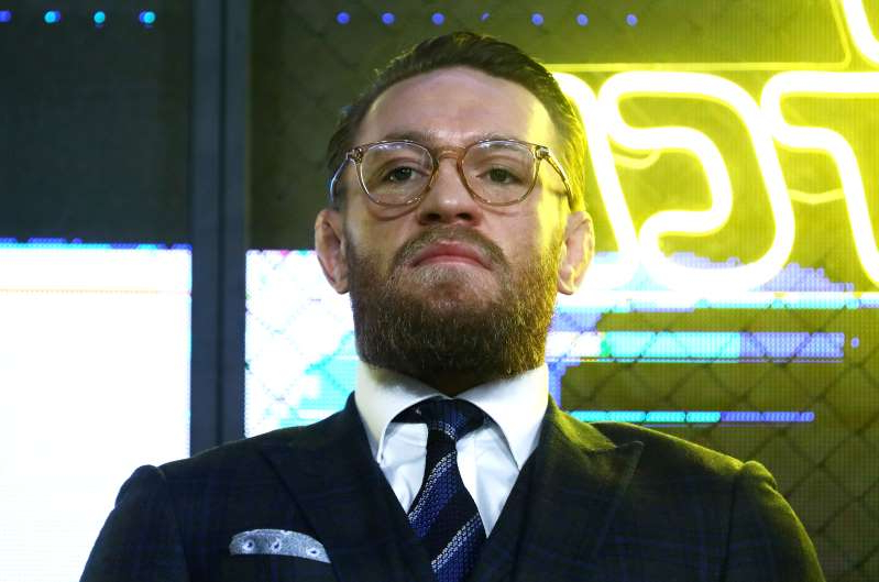 Conor McGregor wearing a suit and tie smiling at the camera: Mixed martial arts (MMA) fighter Conor McGregor attends a news conference in Moscow
