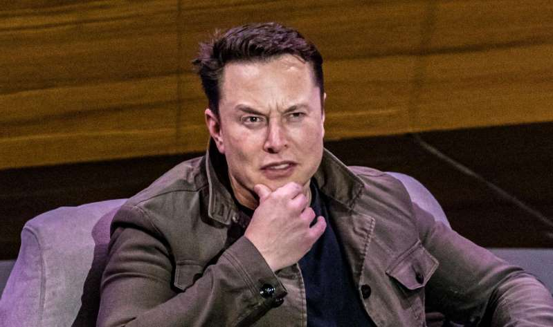 Elon Musk sitting in a chair talking on a cell phone: Elon Musk isn't feeling Twitter right now. James Martin/CNET
