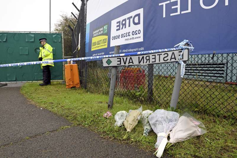 Floral tributes at the Waterglade Industrial Park in Thurrock, Essex, England Thursday Oct. 24, 2019 the day after 39 bodies were found inside a truck on the industrial estate. British media are reporting that the 39 people found dead in the back of a truck in southeastern England were Chinese citizens. (Stefan Rousseau, PA via AP)
