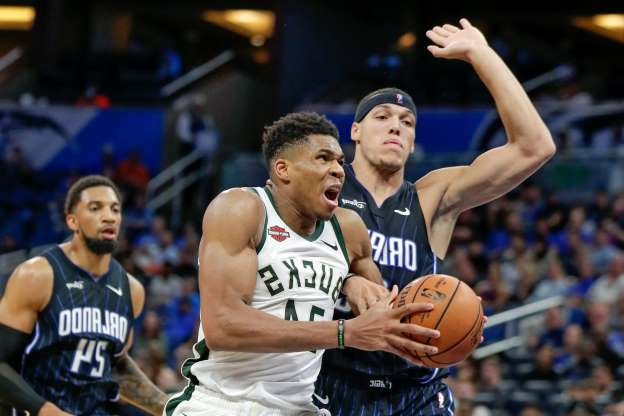 a baseball player holding a basketball: Milwaukee Bucks' Giannis Antetokounmpo goes in for a shot as he gets past Orlando Magic's Aaron Gordon, left, and Khem Birch during the second half of an NBA basketball game Friday, Nov. 1, 2019, in Orlando, Fla. (AP Photo/John Raoux)