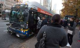 a group of people walking down a street next to a bus: Passengers board a bus in downtown Vancouver, Friday, November, 1, 2019.