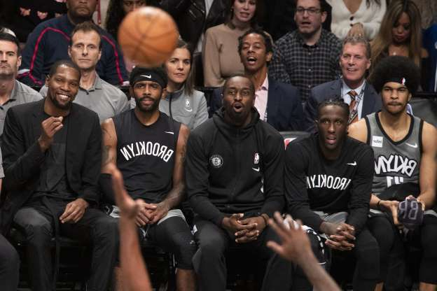 Brooklyn Nets center Jarrett Allen, forward Taurean Prince, guard Theo Pinson, guard Kyrie Irving and forward Kevin Durant, from left, watch from the bench during the second half of the team's NBA basketball game against the Houston Rockets on Friday, Nov. 1, 2019, in New York. The Nets won 123-116. (AP Photo/Mary Altaffer)