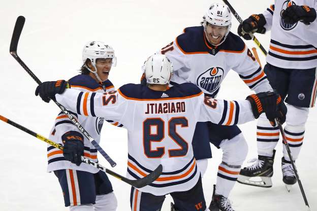 Edmonton's Leon Draisaitl celebrates his winning goal with James Neal (18) and Ethan Bear, right, during the overtime period against Pittsburgh on Nov. 2, 2019. The Oilers won 2-1.