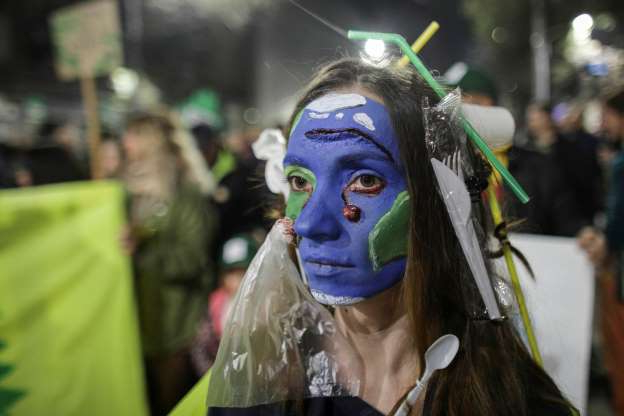 a close up of a person wearing a costume: An activist with her face painted as a waste-ridden planet Earth attends a protest against widespread illegal logging and lack of policy response that has left two foresters dead earlier this year