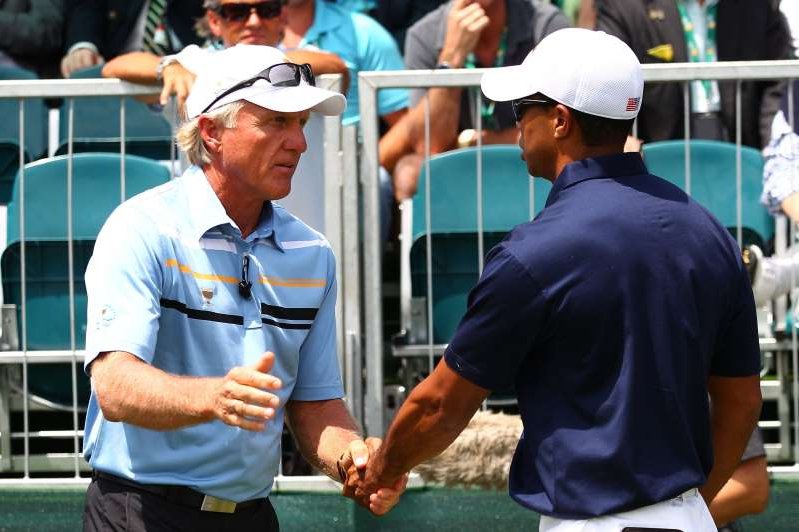a man standing in front of a crowd: Tiger Woods and Greg Norman shake hands at the 2011 Presidents Cup.