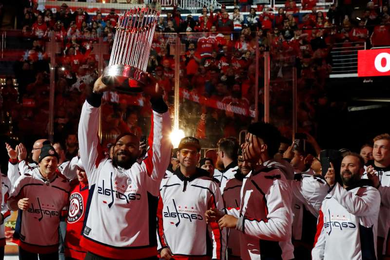 Howie Kendrick et al. standing in front of a crowd: Washington Nationals infielder Howie Kendrick holds the Commissioner's Trophy on the ice during a ceremony honoring the World Series champions.