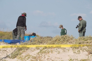 Police identify person of interest in mysterious death of couple buried on beach