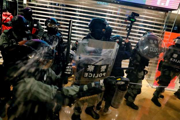 Riot police use pepper spray to disperse anti-government protesters at a shopping mall in Taikoo Shing, Hong Kong