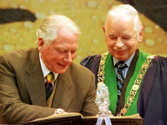 Slide 15 of 26: TV chat show host Gay Byrne signs the Roll of Honorary Freedom, with Lord Mayor Joe Doyle, after being granted the Freedom of the City of Dublin.