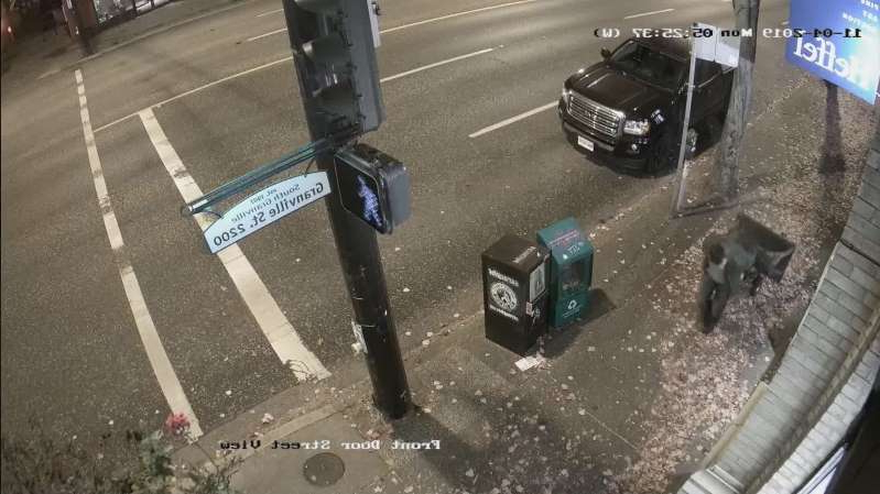 a car parked on the side of a road: Security video shows a man wheeling a $24,000 bronze statue away from a Vancouver art gallery.