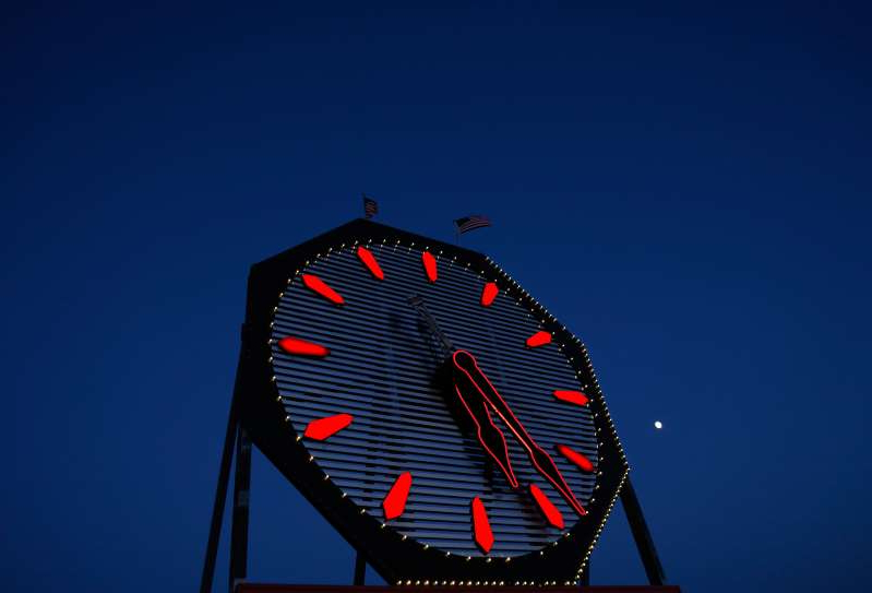 a clock tower in the background: The moon sets behind the Colgate Clock at sunrise on March 24, 2019 in Jersey City, New Jersey. (