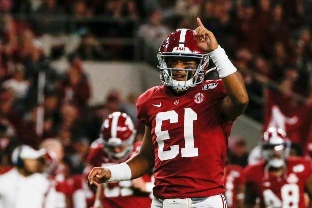 a football player holding a baseball bat: Oct 19, 2019; Tuscaloosa, AL, USA; Alabama Crimson Tide quarterback Tua Tagovailoa (13) celebrates after a touchdown during the first half of an NCAA football game against the Tennessee Volunteers at Bryant-Denny Stadium. Mandatory Credit: Butch Dill-USA TODAY Sports