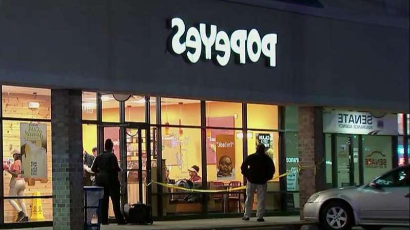 a group of people standing in front of a store: Police investigate stabbing at Popeyes.