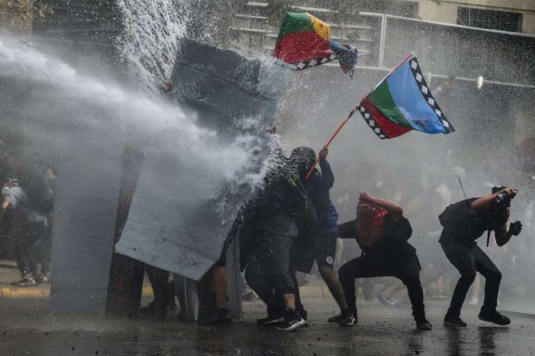 a group of people walking in the rain: Fresh clashes erupted in the Chilean capital Santiago as protests entered their third week