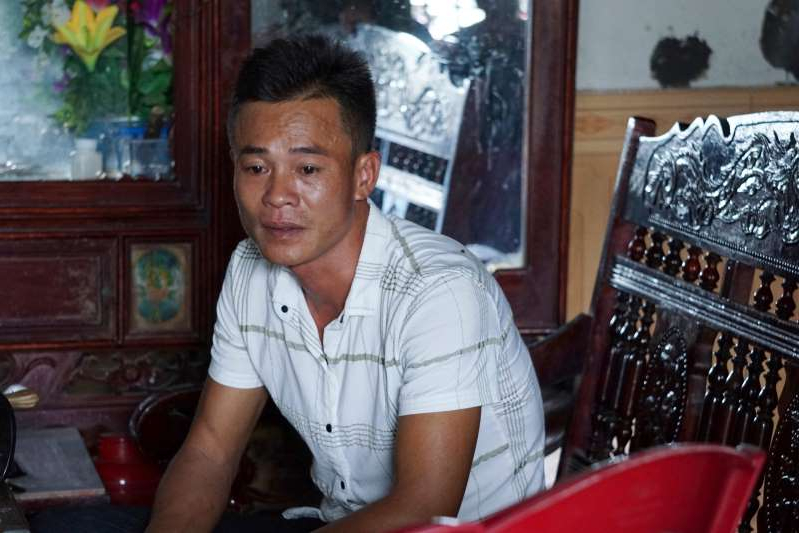 a man sitting at a table in front of a window: Vo Ngoc Chuyen, brother of Vo Ngoc Nam, speaks to media at his home in Yen Thanh district, Nghe An province, Vietnam Sunday, Oct. 27, 2019. Chuyen's family fear that Vo Ngoc Nam could be among the people who died in a container in U.K.