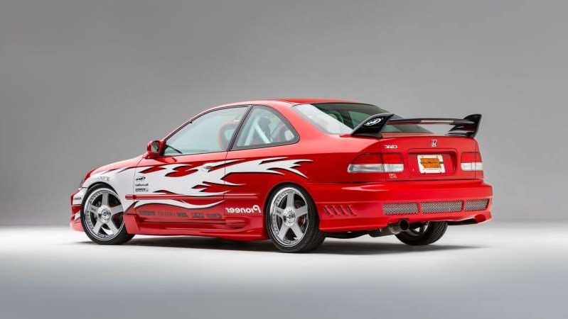 a red car driving on a road: 1999 Honda Civic Si Heritage SEMA Show
