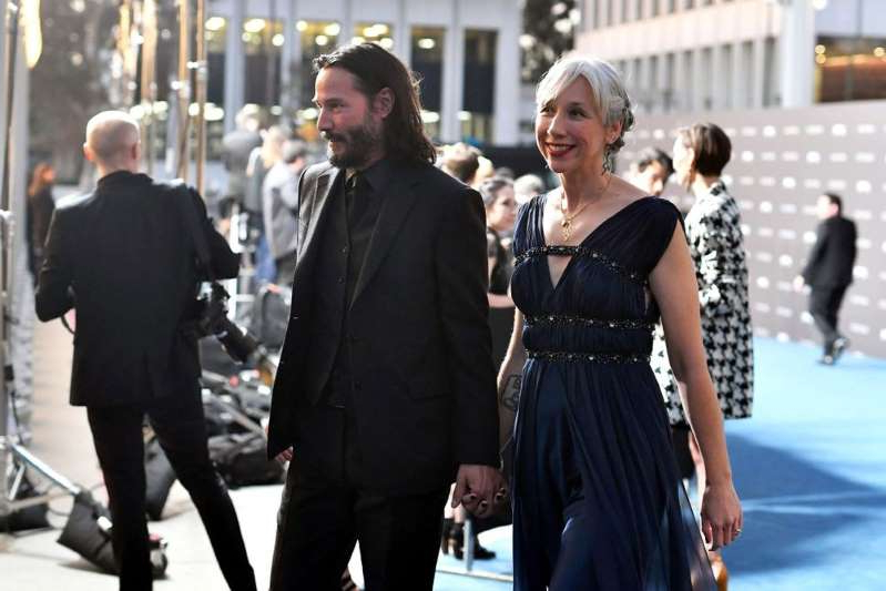 Alexandra Grant et al. that are standing in the street: Alexandra Grant and Keanu Reeves