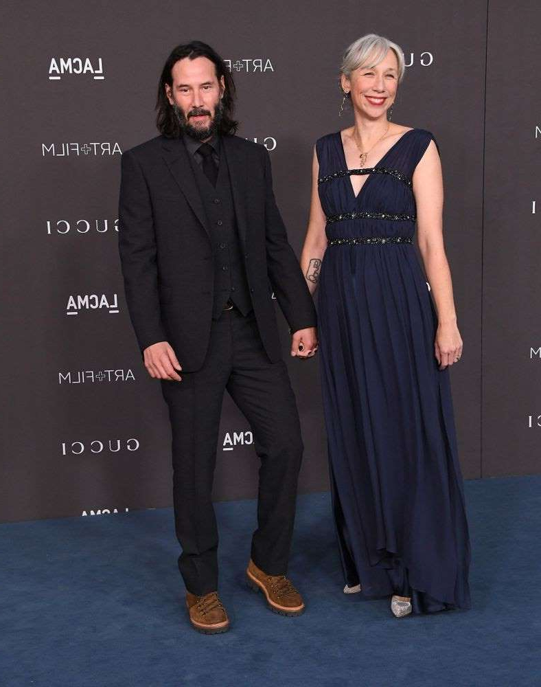 Alexandra Grant, Keanu Reeves are posing for a picture: Alexandra Grant and Keanu Reeves