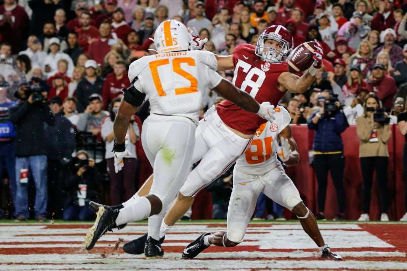 a crowd of people watching a baseball game: Alabama tight end Miller Forristall tries to pull in a reception as Tennessee  linebacker Quavaris Crouch defends.