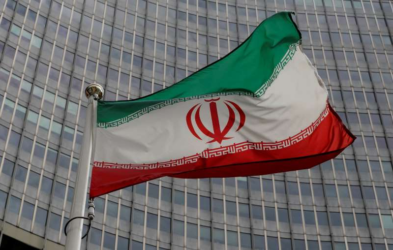 a green and white tiled floor: FILE PHOTO: An Iranian flag flutters in front of the IAEA headquarters in Vienna