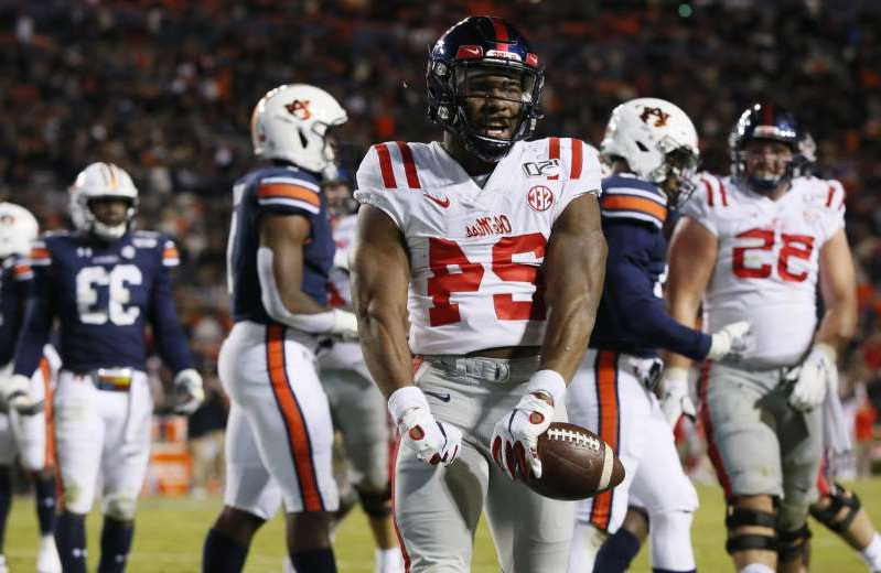 a group of football players: Mississippi Rebels running back Snoop Conner (24) celebrates after scoring a touchdown against the Auburn Tigers during the fourth quarter at Jordan-Hare Stadium on November 2, 2019.
