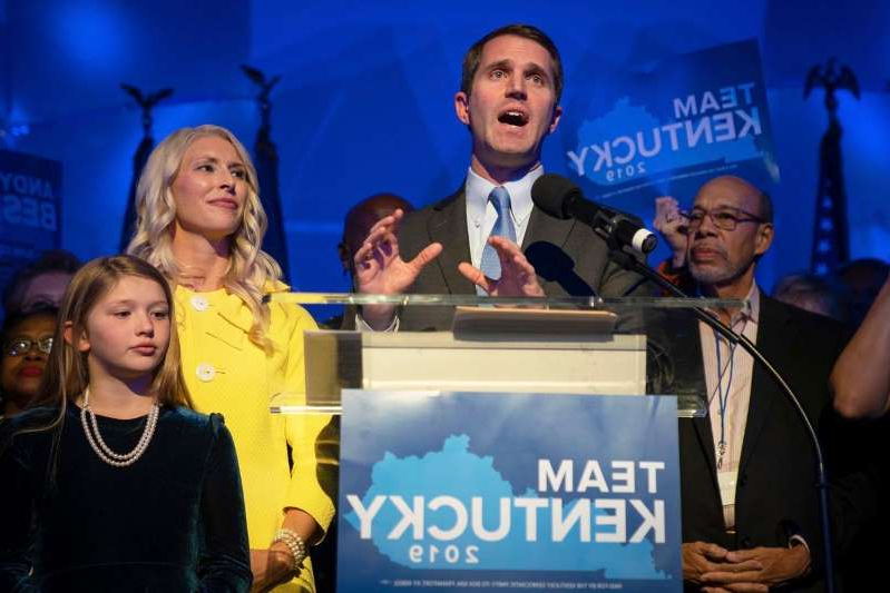 a group of people posing for the camera: Democrat Andy Beshear declared victory in the Kentucky governor's race Tuesday night.