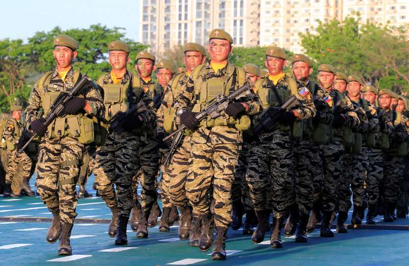 a group of people standing in front of a military uniform: Soldiers march during the 121st founding anniversary of the Philippine Army at Taguig city, Metro Manila