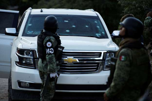 a police car parked in a parking lot: Soldiers assigned to Mexico's National Guard stand by a bullet-riddled vehicle belonging to one of the Mexican-American Mormon families that were killed by unknown assailants, in Bavispe