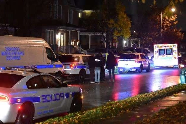 a car parked on the side of a building: Police cordoned off a home in Brampton, Ont., overnight after two young brothers were found dead inside.