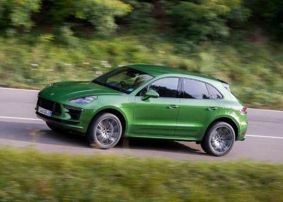 a green car parked on the side of a road: The Turbo is the most powerful version of the Porsche Macan SUV.