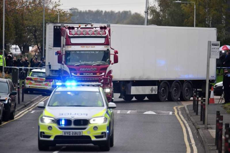 a truck that is driving down the street: Police officers drive away a truck in which 39 dead bodies were discovered on Oct. 23, in the U.K. The victims are believed to be Vietnamese nationals. Ben Stansall—AFP/Getty Images