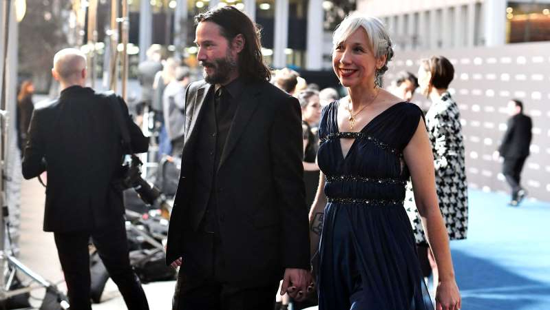 Alexandra Grant et al. walking down the street talking on a cell phone: Alexandra Grant and Keanu Reeves attended the LACMA Art and Film Gala on Saturday.