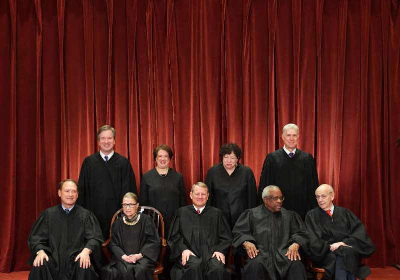 Stephen Breyer, Neil Gorsuch, Clarence Thomas, Sonia Sotomayor, John Roberts, Elena Kagan, Ruth Bader Ginsburg, Brett Kavanaugh, Samuel Alito standing in front of a curtain: The current justices of the U.S. Supreme Court pose for a group photo on November 30 2018.