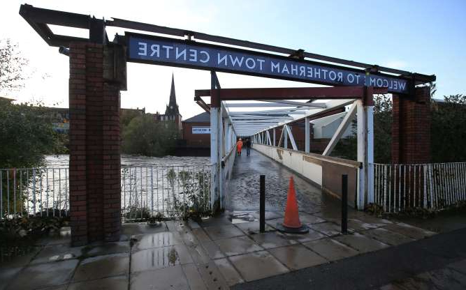 a bridge over a body of water: View of a bridge after floodwaters rose in Rotherham, near Sheffield