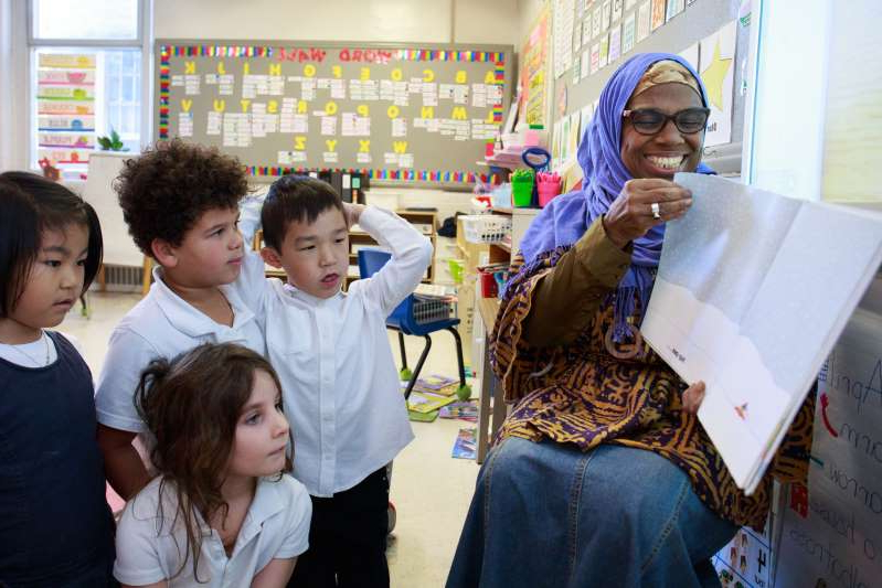 a group of people looking at a book: Haniyfa Scott reads to her Carlyle School class in the Town of Mount Royal, Quebec, on Oct. 29, 2019 (Nasuna Stuart-Ulin)