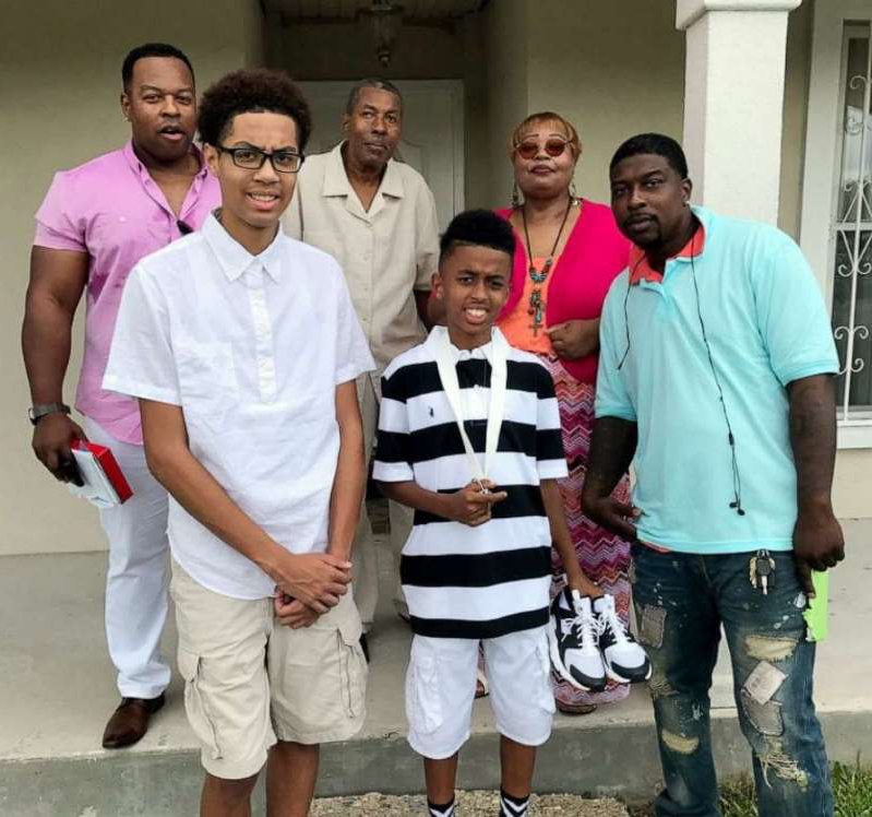 a group of people posing for the camera: Quinnyon Wimberly, mother Irene Wimberly, son Quinnyon Wimberly II, father Frank Wimberly Sr., nephew Jordan Wimberly and brother Frank Wimberly Jr. pose for a family photo.