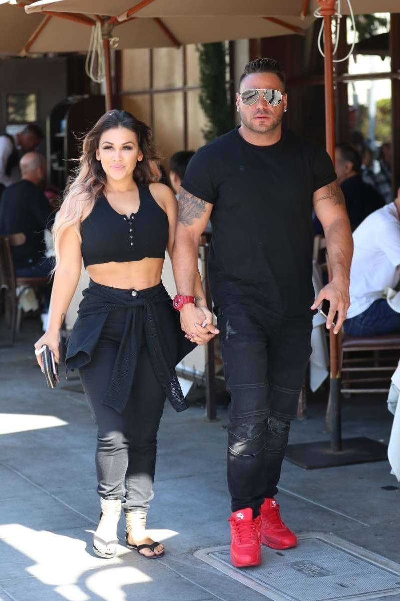 a man and a woman standing in front of a building: Ronnie Ortiz-Magro and girlfriend Jen Harley hold hands in Beverly Hills on Oct. 3, 2019, before his arrest for alleged domestic violence later that evening.