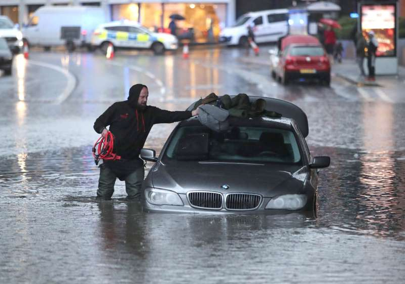 a person driving a car: A man with a car in a flooded street in Sheffield (Danny Lawson/PA)