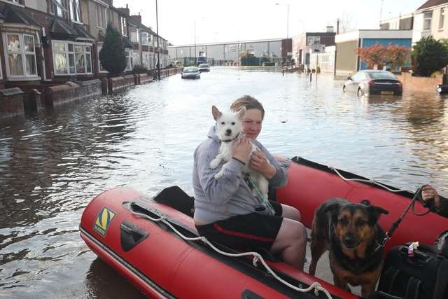 a person sitting on a boat with a dog: A dog is carried to safety on Yarborough Terrace in Doncaster, as residents flee their homes (Danny Lawson/PA)