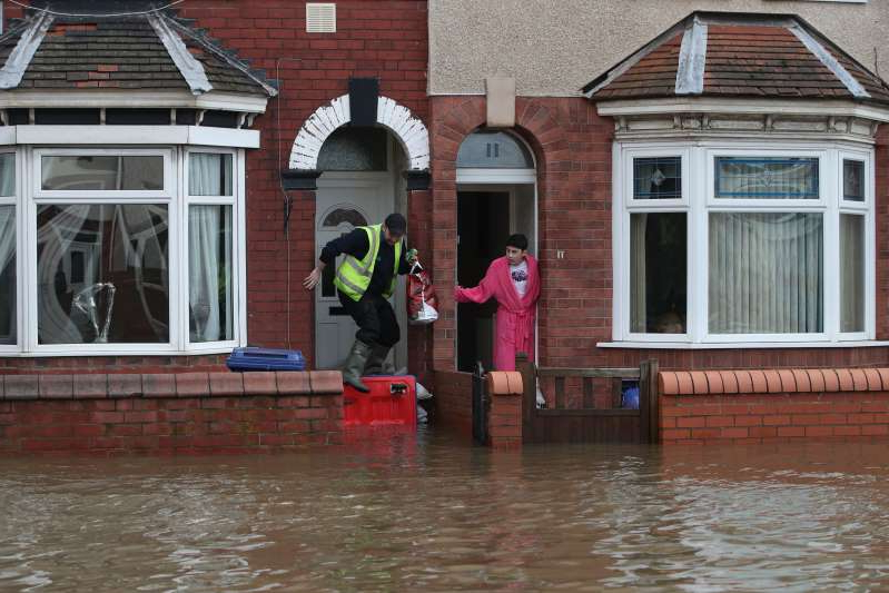 a person standing in front of a building: People try to negotiate floodwater in Yarborough Terrace in Doncaster, South Yorkshire, as parts of England endured a month's worth of rain in 24 hours (Danny Lawson/PA)