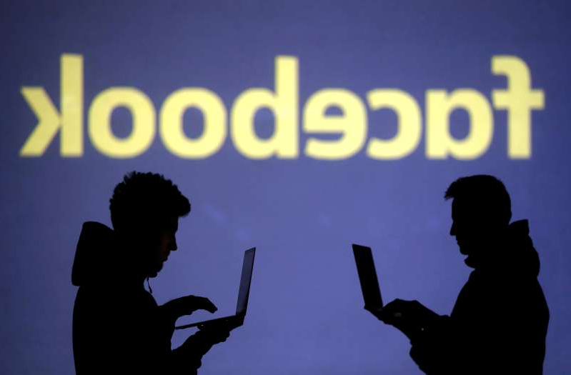 a person standing in front of a sign: FILE PHOTO: Silhouettes of laptop users are seen next to a screen projection of a Facebook logo