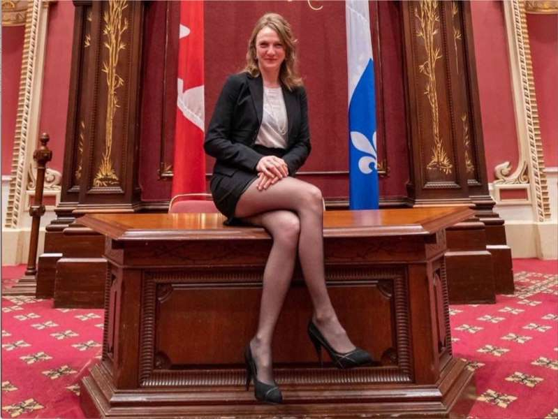 a person standing in front of a store:  Québec solidaire MNA Catherine Dorion sits on the main desk of the Salon rouge at the National Assembly in Quebec City, in a photo she posted to Facebook on Oct. 31, 2019.