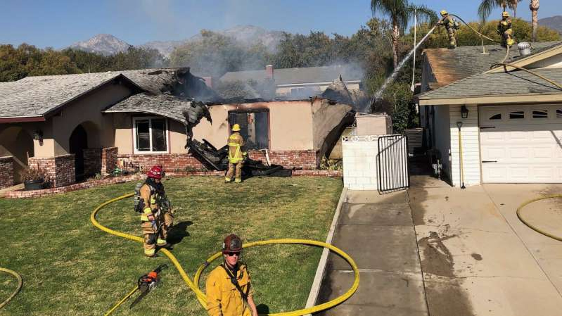 a person with a bicycle in front of a house: A single-engine airplane flew into a home in California on Thursday morning, killing the pilot in a fiery crash.