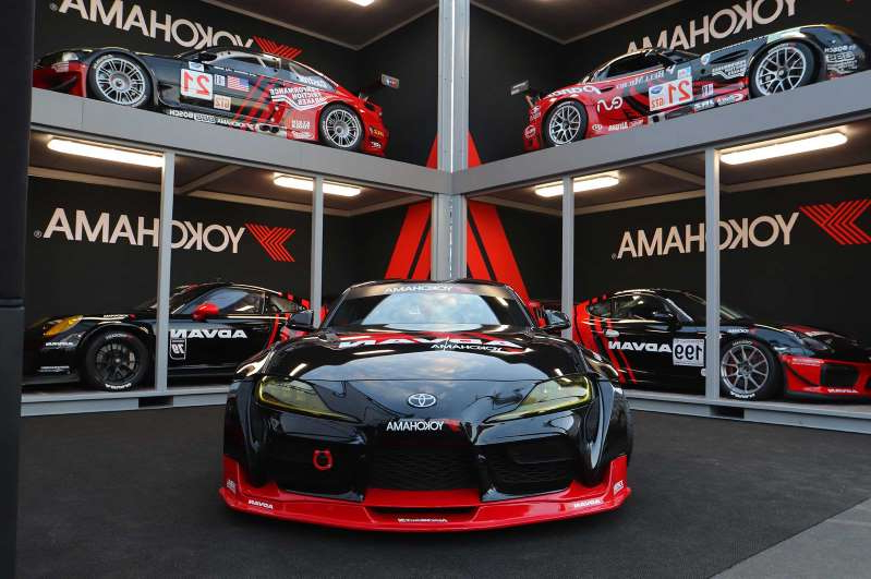 a red car parked on the side of a building: Yokohama-2019-SEMA-Booth-Supra