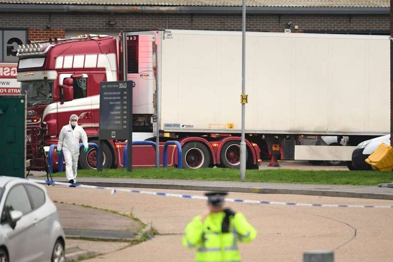 a truck is parked on the side of a road: The container lorry where 39 people were found dead inside leaves Waterglade Industrial Park in Grays, Essex