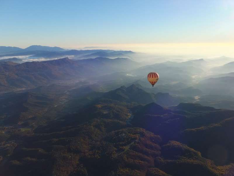 a view of a large mountain in the background: Hot-air ballon riders take in the scenic views of Garrotxa Volcanic Natural Park Catalonia.
